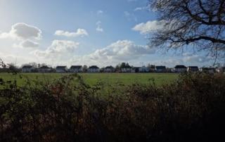 Ligne de maisons marquant la limite du hameau en arrière-plan, derrière un champ et une haie au premier plan