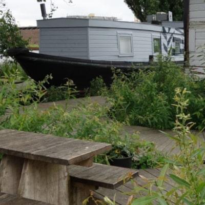 Péniche blanche rénovée en locaux professionnels, ponton et table en bois