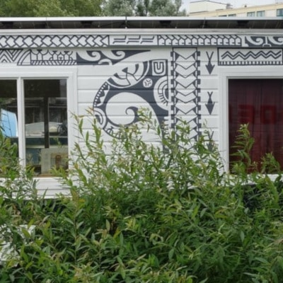 Péniche blanche à motifs noirs, rénovée en locaux professionnels