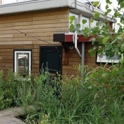 Péniche rénovée en locaux professionnels, entourée de végétation haute
