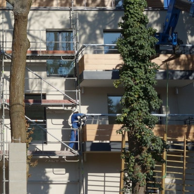 Ouvrier et échafaudage d'un chantier derrière des arbres