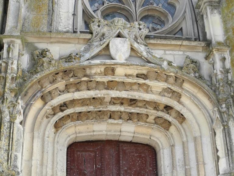 Nids d'hirondelle accrochés au porche d'une église
