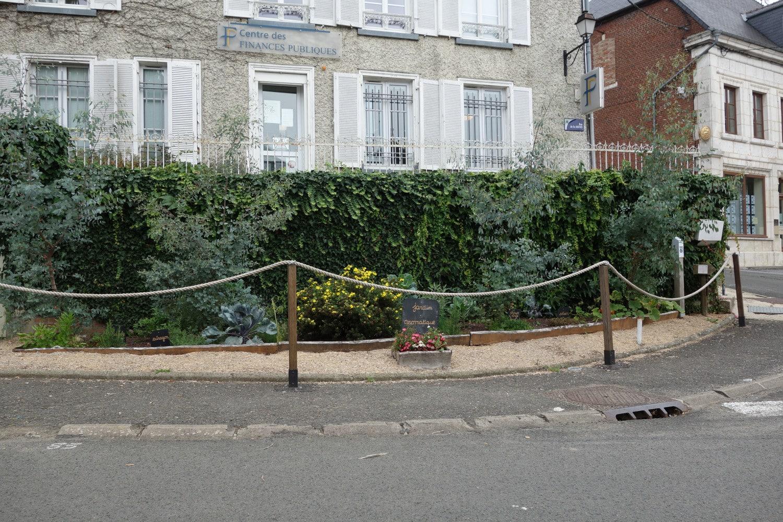 """Potager urbain sur un trottoir, pancarte indiquant """"jardin aromatique"""""""