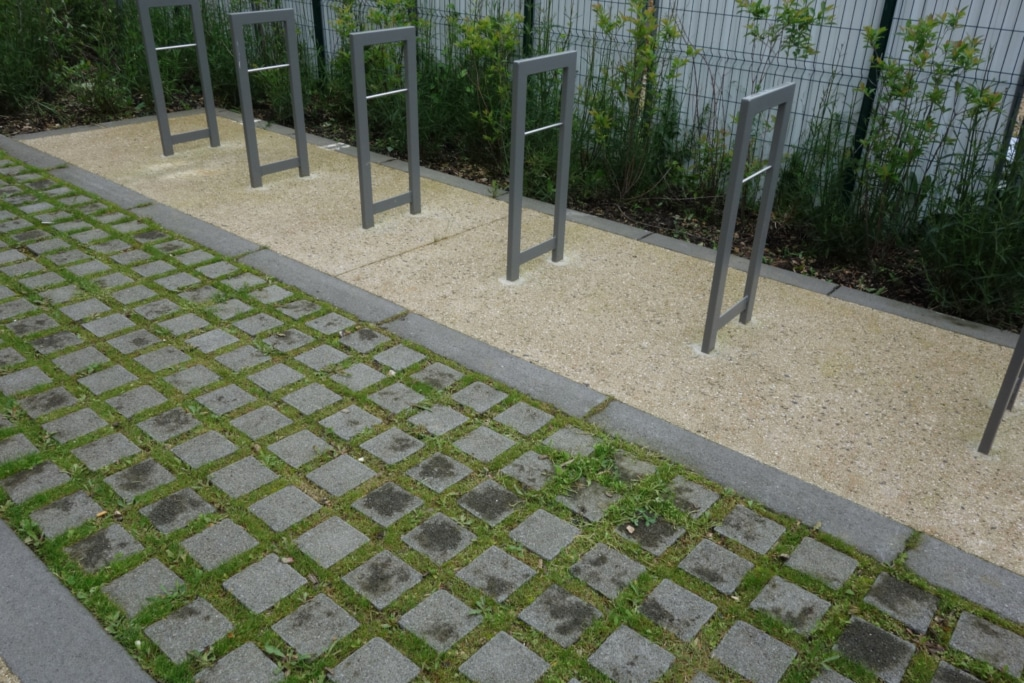 Parking vélo en pavés non jointifs entre lesquels poussent de l'herbe