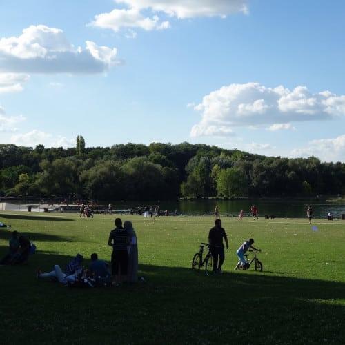 Visiteurs du parc pratiquant des activités de loisirs sur la pelouse au bord d'un étang